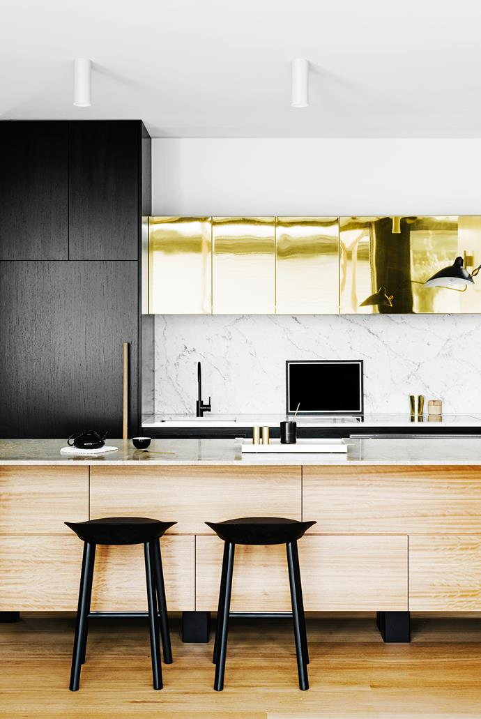 """**Top brass –** a luxurious stretch of gleaming polished brass heightens the sophisticated glamour of this Melbourne kitchen. The brass sheeting used to clad the overhead cupboards was a stroke of genius by interior designer [Fiona Lynch](http://www.fionalynch.com.au/?utm_campaign=supplier/