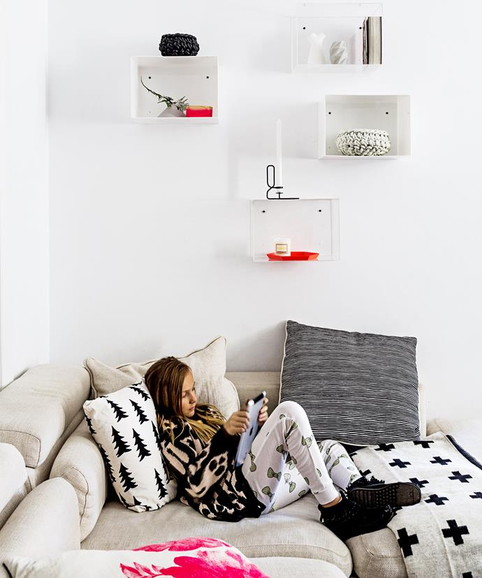 "Renata's daughter Sophie makes herself comfortable on the sofa. The Perspex wall boxes showcase special finds, while the Scandi-style cushions fit with the home's interior decoration.  Gran Fir Tree **cushion cover** in Black from [Talo Interiors](http://talointeriors.com.au/?utm_campaign=supplier/|target=""_blank"") ."