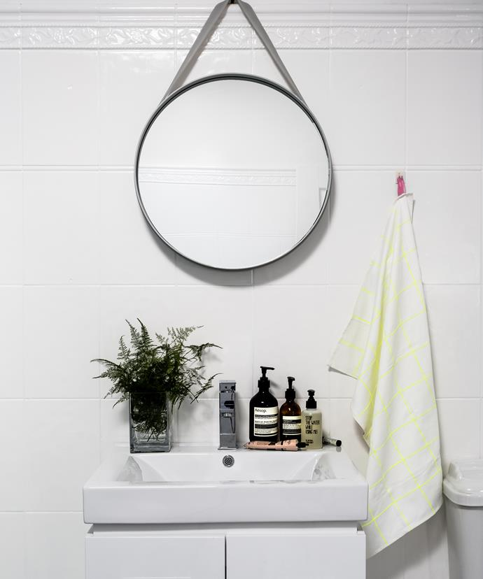 Neon details inject an element of surprise in the otherwise monochrome bathroom.