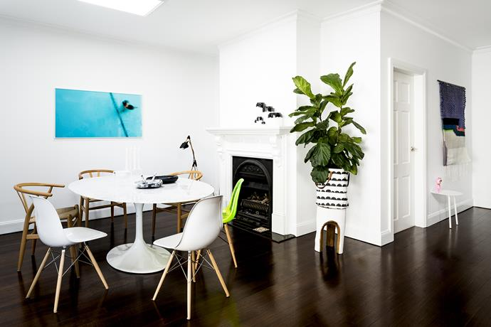An uncluttered dining area makes the space feel bigger than it is, while the lush green plant is eye-catching against all-white walls.