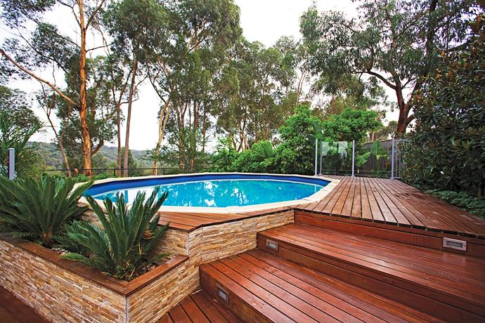 With clever decking, above-ground pools can look as amazing in-ground pools. Here, decking and semi-frameless glass fencing elevate the look of this above-ground swimming pool.
