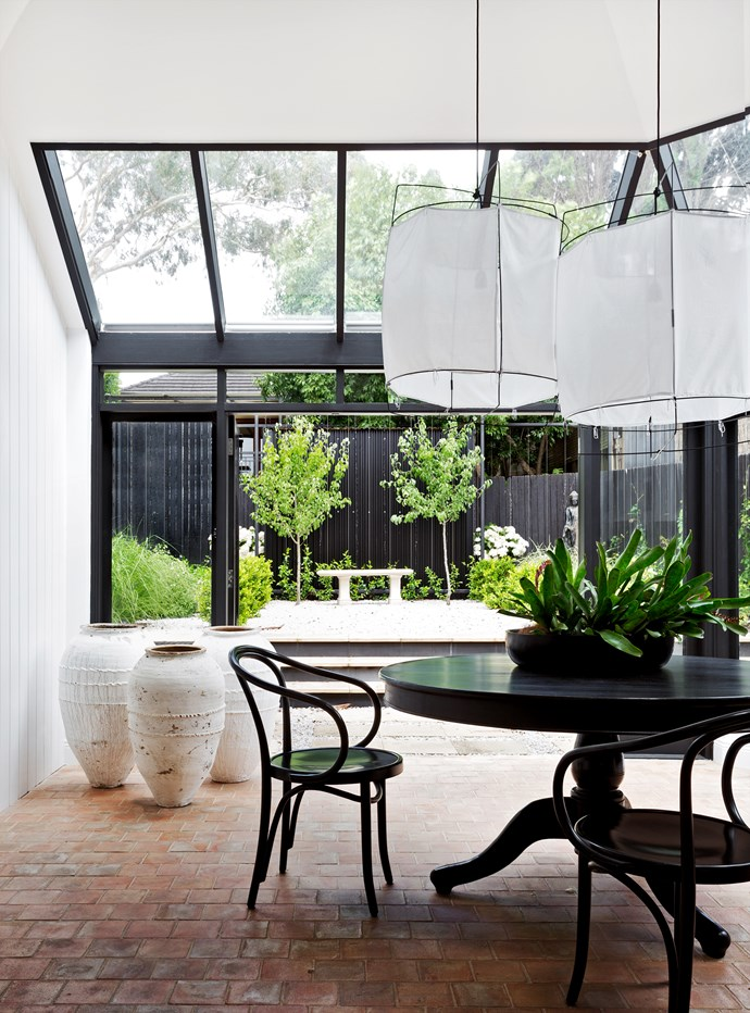 "The atrium, added to the home during its previous renovation, overlooks a **garden** by [Peter Fudge Gardens](http://peterfudgegardens.com.au/?utm_campaign=supplier/|target=""_blank"").   Thonet 'Le Corbusier' **armchairs**. Existing **dining table** was stained black. White **lampshades** and **urns** from [Les Interieurs](http://www.lesinterieurs.com.au/?utm_campaign=supplier/