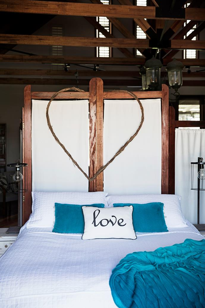"The bedrooms are furnished with white bedlinen. This 'room' backs onto the studio living area and is divided with a screen made by Lorraine's partner Michael. ""The heart above the bed is one of my favourite bargains. I got it at a garage sale for $10,"" says Lorraine."