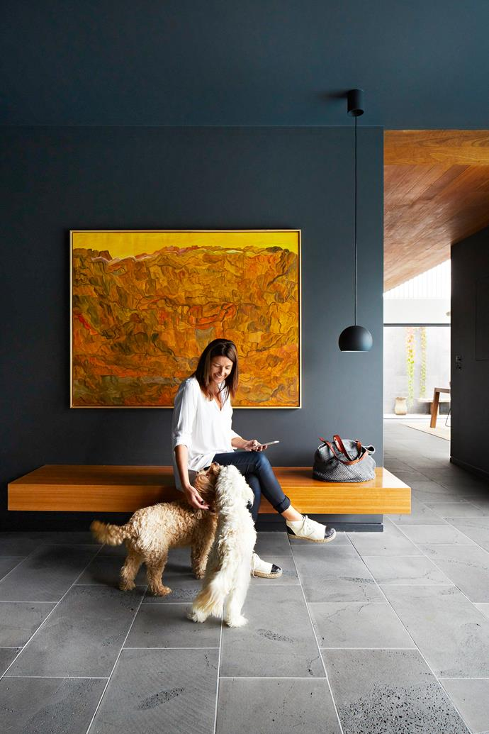 """Homeowner Tanya Mendel enjoys the attention of Bailey the spoodle (left) and Millie the cavoodle. Blackbutt joinery details are woven into the fabric of the house. Here in the foyer, it's formed into a built-in bench.   **Pendant** from [Sonic Lighting](http://www.soniclighting.com.au/?utm_campaign=supplier/