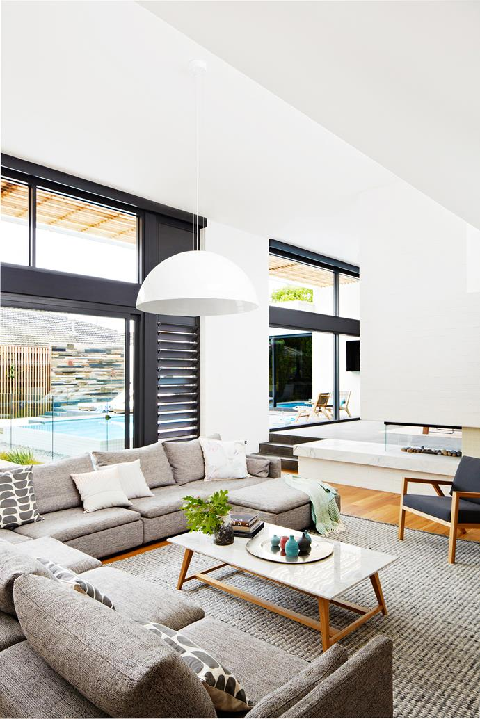 """Black window frames and louvres draw all eyes to the pool.  Vittoria Polo **sofa** and Sloan marble **coffee table**, both from [Globe West](http://www.globewest.com.au/?utm_campaign=supplier/