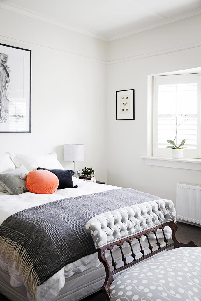 A reupholstered chaise lounge, which once belonged to Claire's grandmother, sits at the end of the couple's bed. Plantation shutters provide varying degrees of light and privacy.