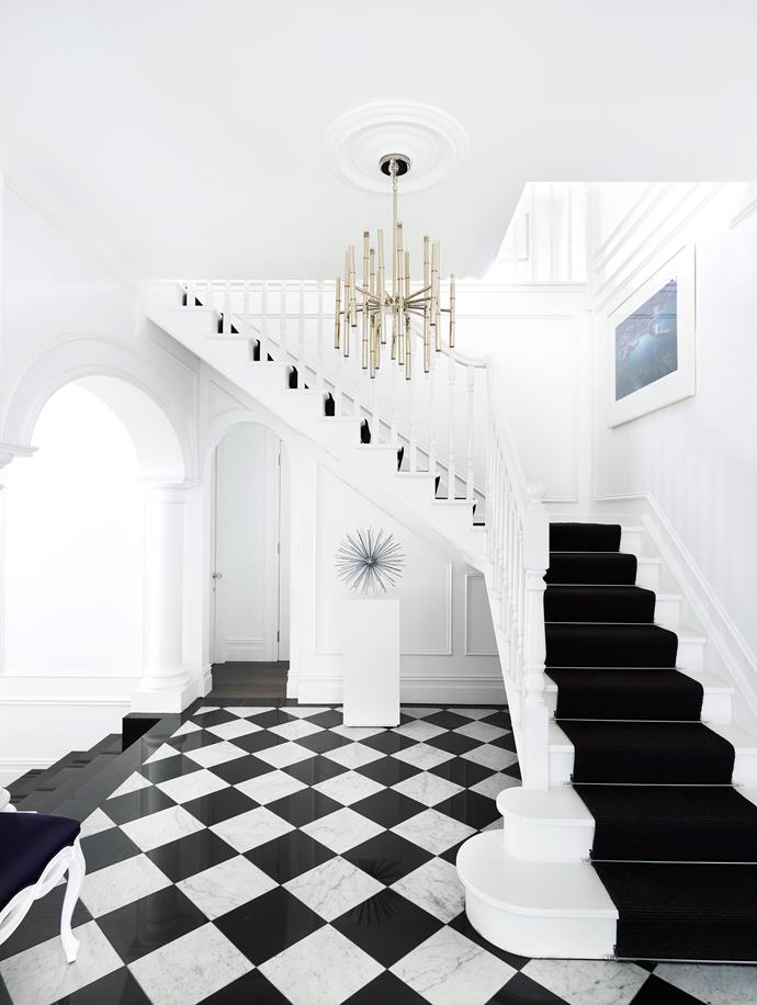 "The imposing entry sets the scene for the whole house. The interiors are a blend of different styles, but Hollywood Regency is the predominant one. ""Without being ostentatious, it's classic with a sense of drama, but it also makes me feel comfortable,"" says Emma. C. Jeré *Sputnik* **sculpture** and Meurice **chandelier** in the entry hall, both from [Jonathan Adler](http://www.jonathanadler.com/?utm_campaign=supplier/