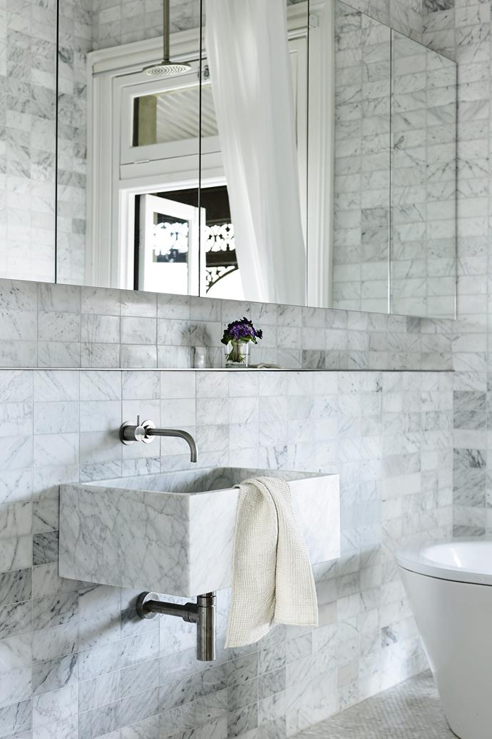 In the main bathroom, the basin was clad in Carrara marble to match the custom-made wall and floor tiles, while a wall of mirrored cabinetry provides ample storage.