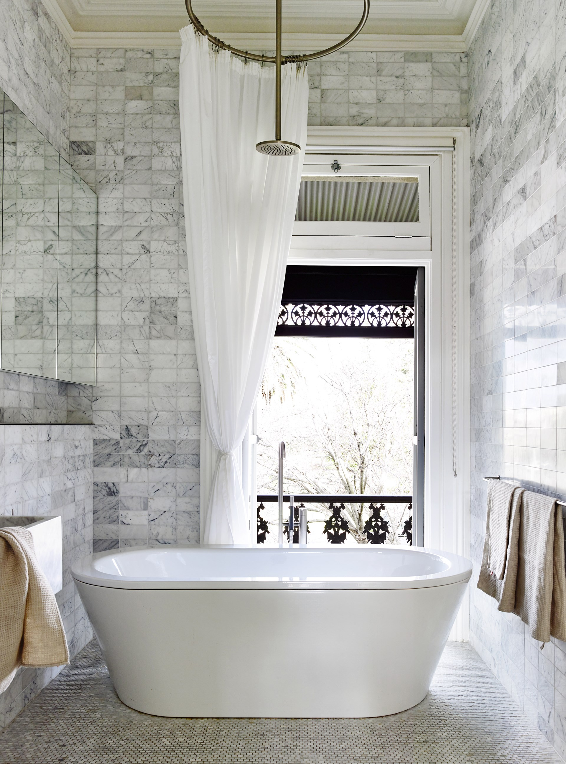 """Carrara marble tiles, French doors, plus a freestanding bath – there is a lot to love about this bathroom within a [Victorian-era terrace](http://www.homestolove.com.au/gallery-annick-and-stephens-chic-terrace-extension-2327