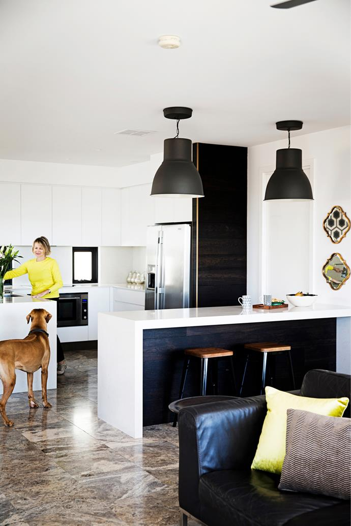 """The monochrome scheme continues in the kitchen with white Caesarstone benchtops and black pendants from [Ikea](http://www.ikea.com/au/?utm_campaign=supplier/