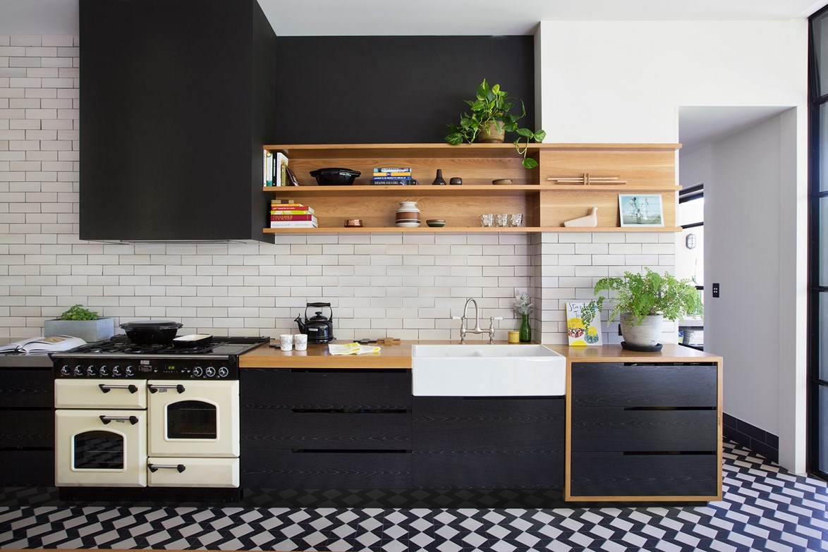 "The owners of this [unique kitchen]((http://www.homestolove.com.au/john-and-kylies-unique-kitchen-renovation-2344/?utm_campaign=supplier/|target=""_blank"") added warmth to the black veneer cabinets with the use of American oak insets and off-white subway tiles. *Photo: James Knowler*"