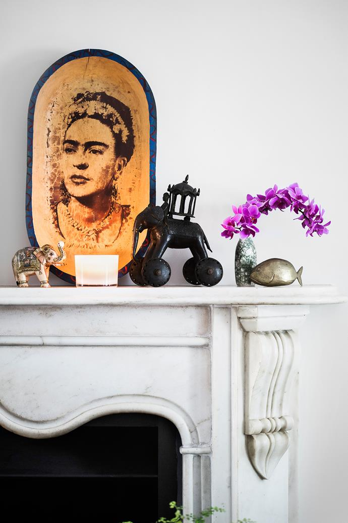 A carved bowl bearing the portrait of Frida Kahlo takes pride of place on the mantelpiece.