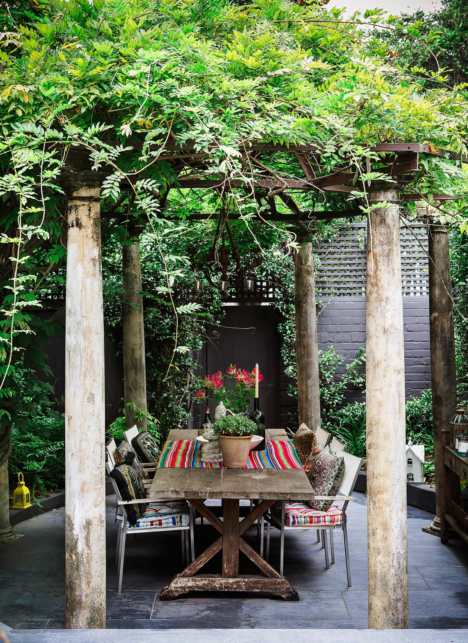 """A wisteria-draped pergola over an antique table sets the scene for alfresco dining at the home of designer [Camilla Franks](https://www.camilla.com.au/?utm_campaign=supplier/