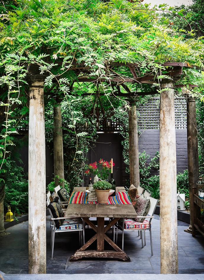 "The wisteria-covered pergola is an idyllic spot for alfresco dining. ""This house speaks to my hosting heart,"" says Camilla. ""I love cooking up a feast in the kitchen and entertaining friends in the garden."" The table is antique."