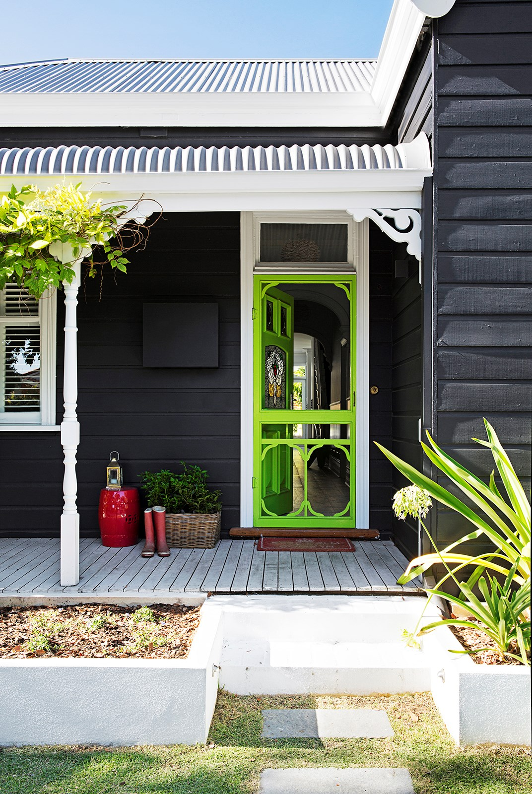 """Both the front door and the flyscreen have been painted in eye-catching Dulux Effervescent Lime to stand out against the grey [weatherboard exterior of this renovated cottage](https://www.homestolove.com.au/gallery-kirk-and-suzannes-perth-cottage-renovation-2323