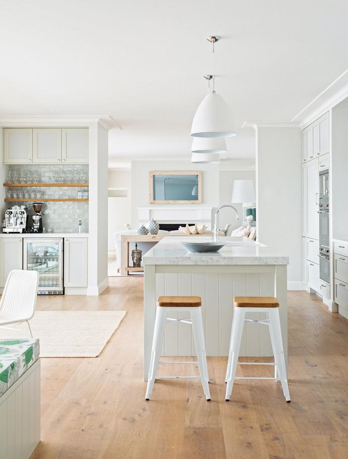 Timber accents add warmth to the crisp white palette used throughout the open plan kitchen and dining room.