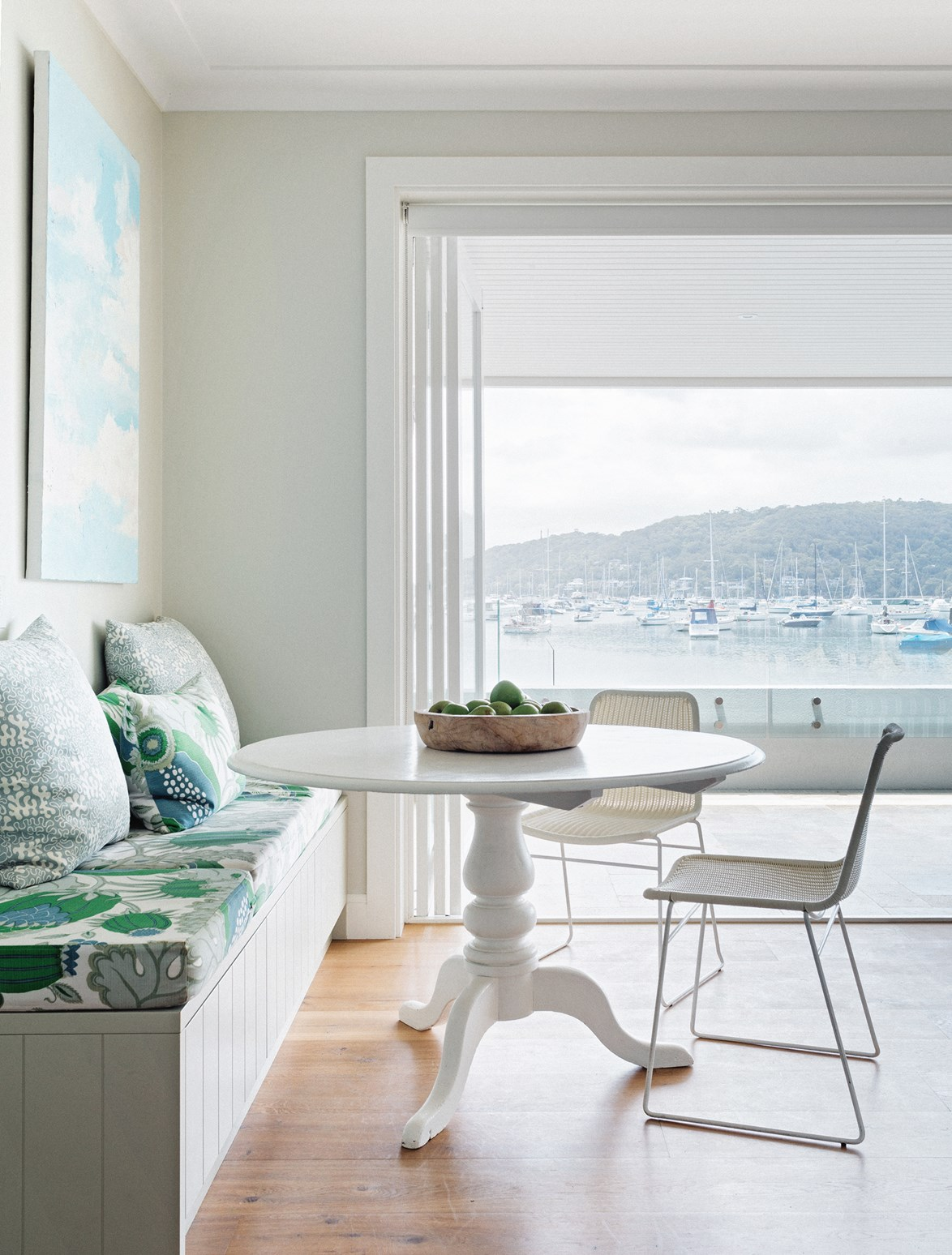A simple artwork and patterned seat cushion add vibrancy to this monochromatic dining nook. *Photo: Felix Forest*