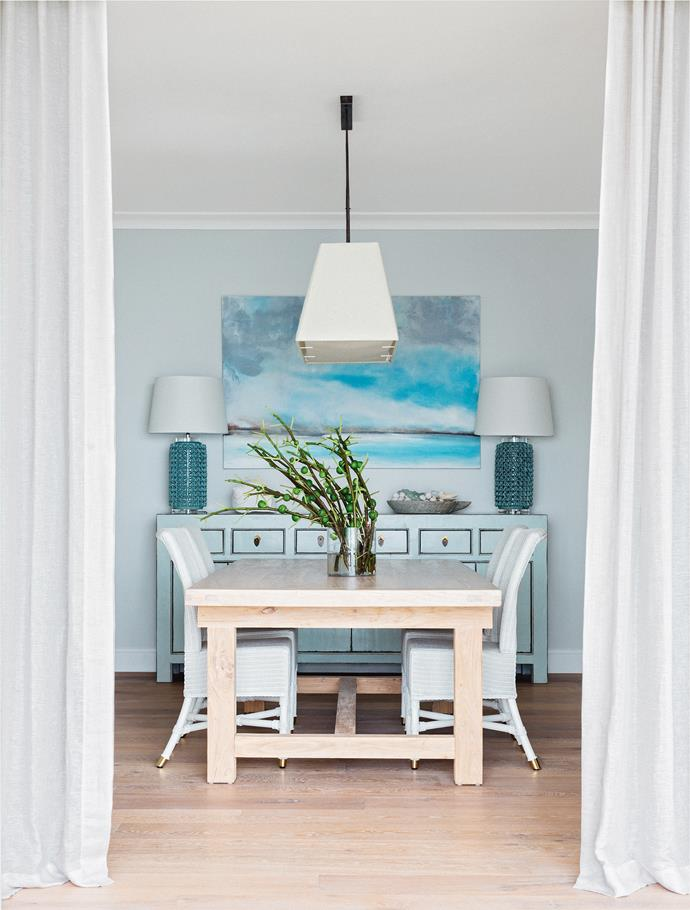 White wicker dining chairs allow the timber dining table to shine, while blue accent pieces and artwork signal the home's beachy surroundings.