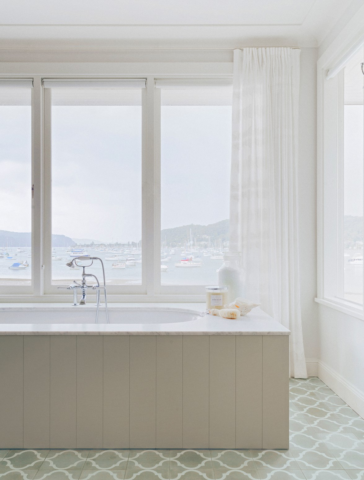 "Even if space isn't a concern – as is the case with this bathroom in a [hamptons style beach house](https://www.homestolove.com.au/hamptons-style-beach-house-renovation-2380|target=""_blank"") – a built-in bath can still steal the show. This soaking tub commands the room while custom panelling blends in perfectly with the home's coastal look. *Photo: Felix Forest / Styling: Lucy McCabe / Story: Belle*"