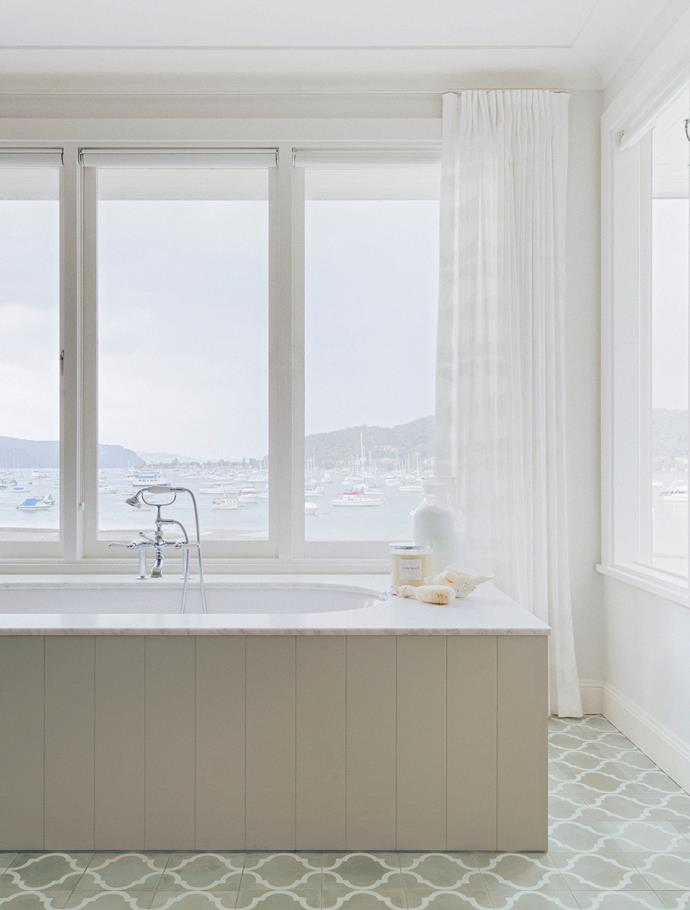 Million dollar views of the ocean can be viewed from the comfort of the home's freestanding bath tub, which has been clad in panelling. Sheer curtains soften the room and add privacy.
