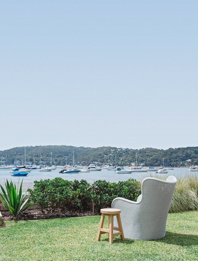 A wicker chair and stool on the back lawn is the perfect place to sit and enjoy the water views.