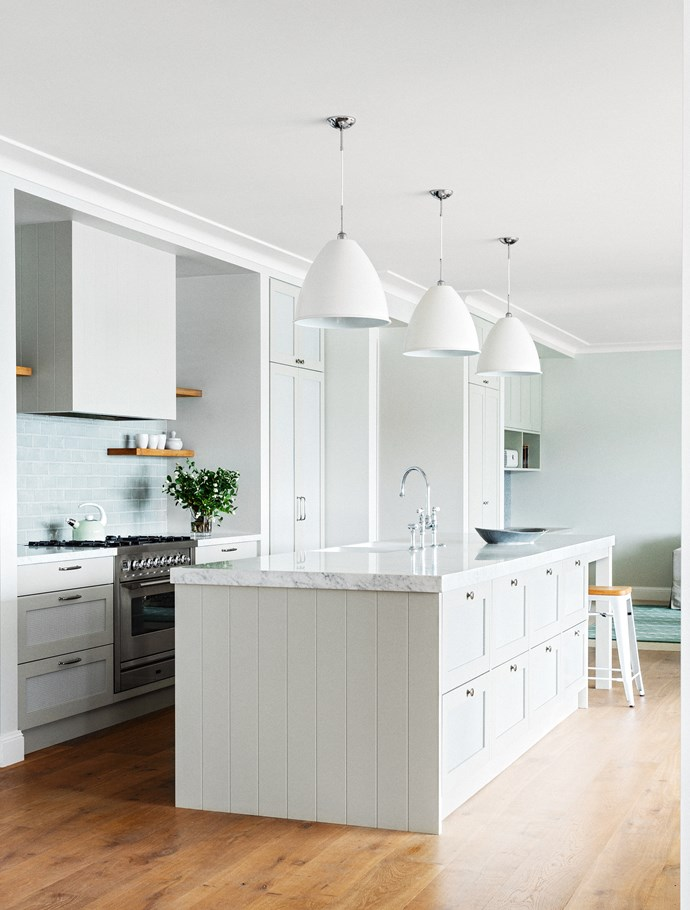 """Matte white pendants hang above a carrara marble benchtop in the kitchen of this [Hamptons style home](https://www.homestolove.com.au/hamptons-style-beachfront-home-2378