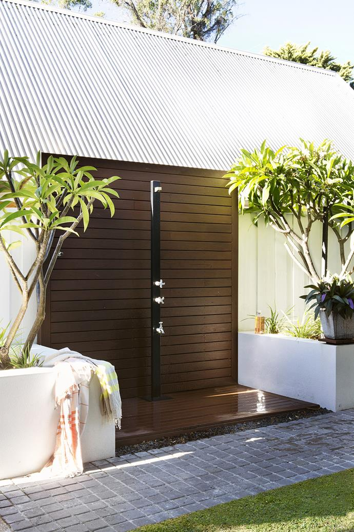 """Frangipani trees frame an outdoor shower in the courtyard. The timber used throughout is hardy native jarrah from [AusWest Timbers](http://auswesttimbers.com.au/?utm_campaign=supplier/