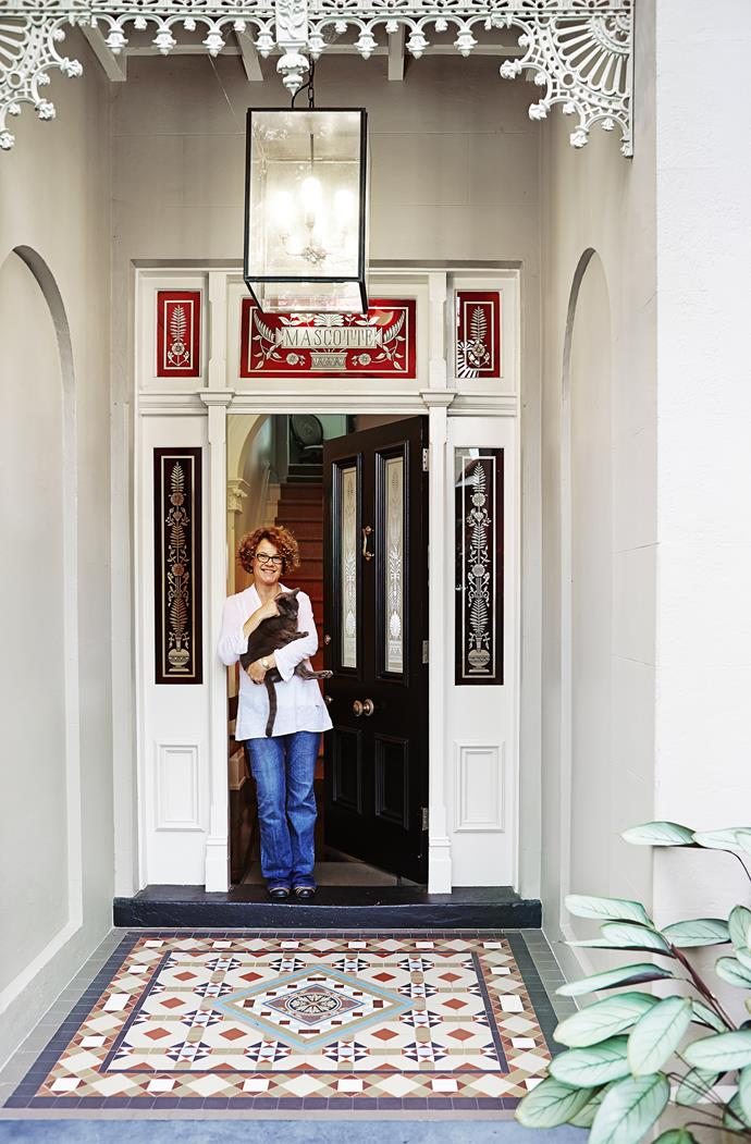 Homeowner Sarah Bice cuddles the family's Russian blue cat, Pushkin, at the entry to her Italianate terrace.