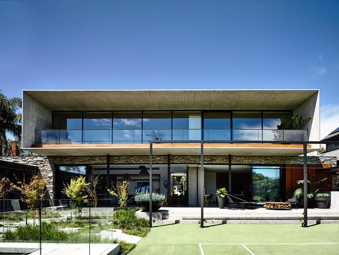 """The home's top-heavy facade features two strong and powerful blades that have been truncated and slightly tapered to 'soften' the edges. """"There is a plasticity to concrete – it just depends on what you do with it,"""" says Matt. The cantilevered concrete planes serve to deflect the sun and encourage views of the rear garden, tennis court, swimming pool and cabana."""