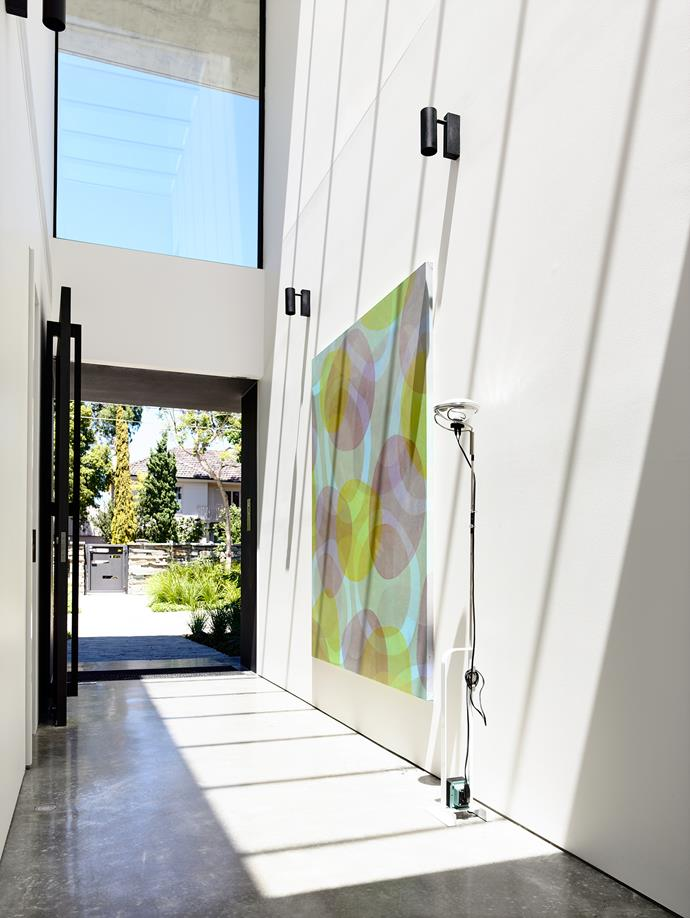 """The home's front door opens into a double-height entry gallery flooded with sunlight. *Organic Grapes* **artwork** by Sarah Leslie from [Thierry B. Gallery](http://www.thierrybgallery.com/?utm_campaign=supplier/