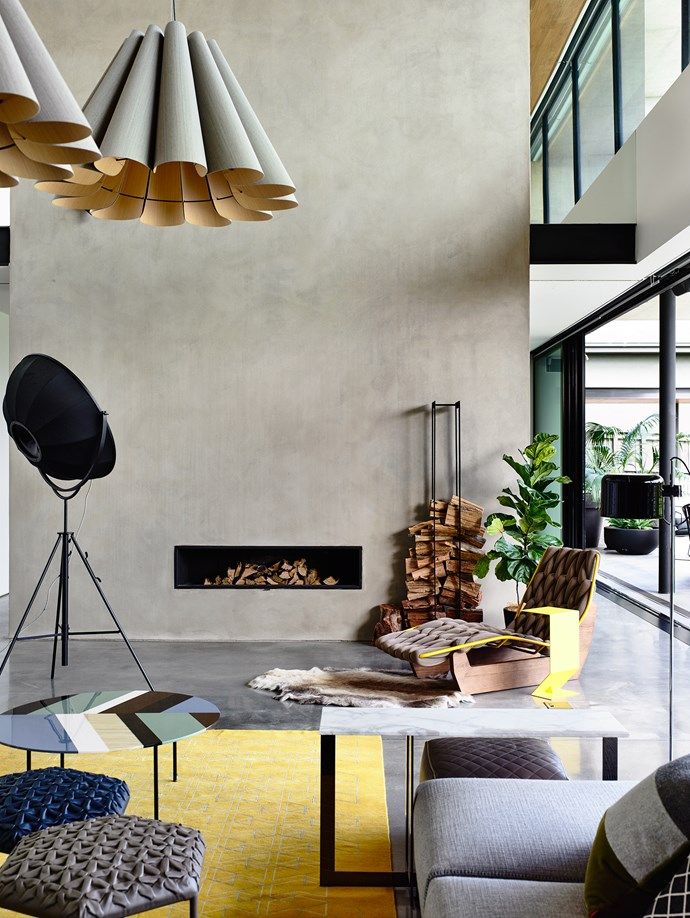 """The double-height polished plaster chimney is not just for aesthetics, but a stark reminder that this is Melbourne – not LA or the tropics. Serving as something of a partition, it divides the ground floor into two living spaces, and soars up the core of the house, bisecting the childrens' retreat on the second floor. Patricia Urquiola Fishbone **table** and Mark yellow **side table** by [Moroso](http://www.moroso.it/?utm_campaign=supplier/