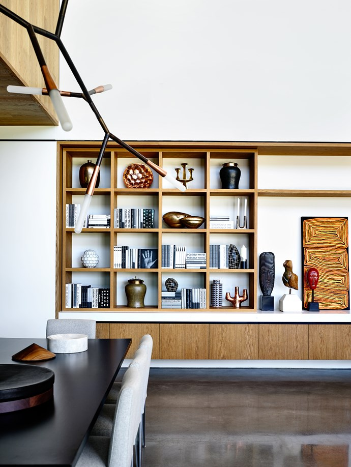 A built-in joinery unit made from engineered oak marks the crossover from living to kitchen, with the ceiling height, dimensions and materiality changing in the new area.