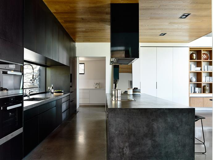 A heavy rangehood hangs over a thick, grey concrete island bench in the kitchen.