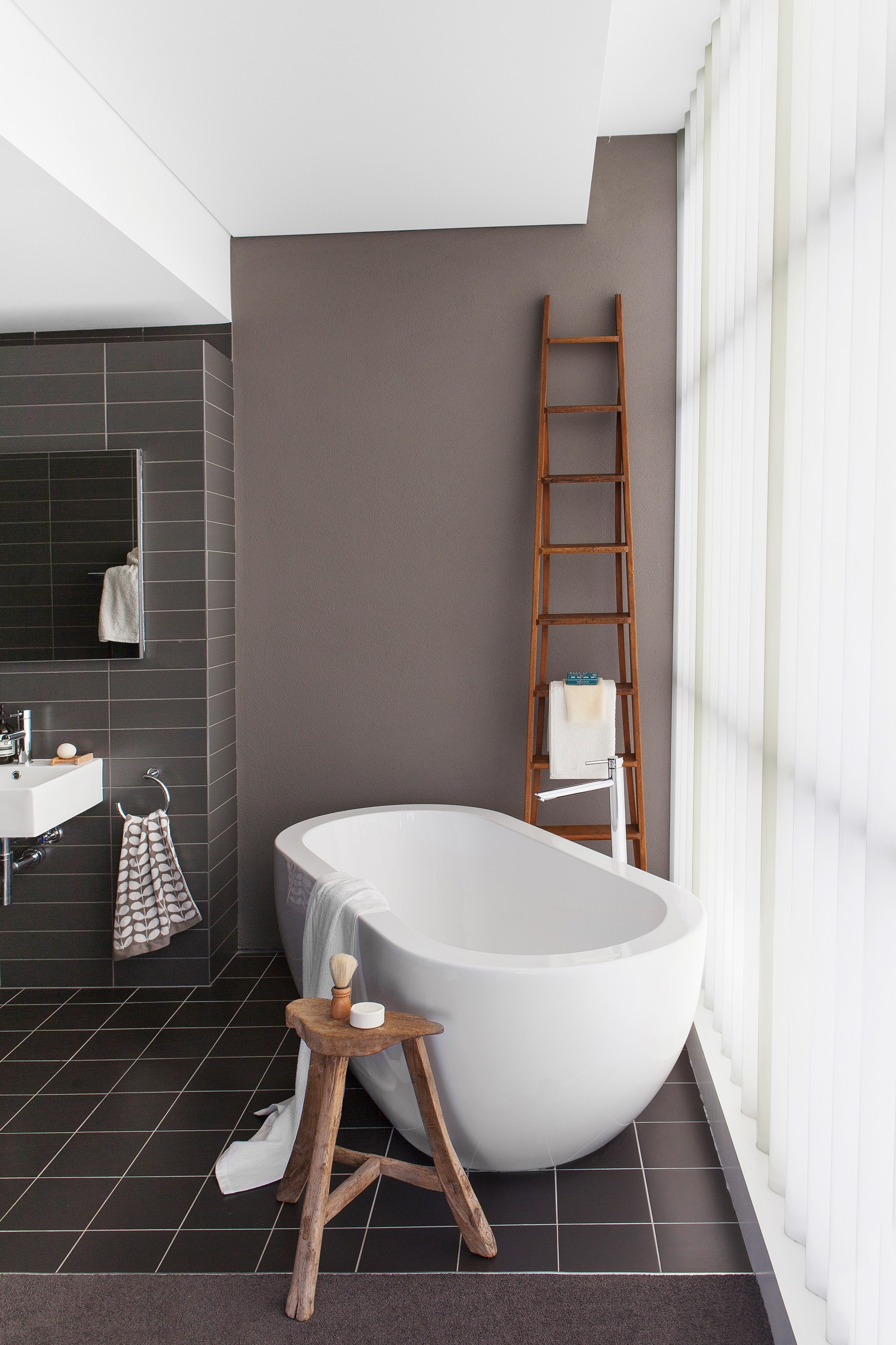 "Dark colours were used to clearly delineate the ensuite zone in the open plan master bedroom of this [pre-fab country home](http://www.homestolove.com.au/gallery-pierina-and-josephs-dream-home-in-country-victoria-2438|target=""_blank""). Photo: Simon Griffiths / *Australian House & Garden*"