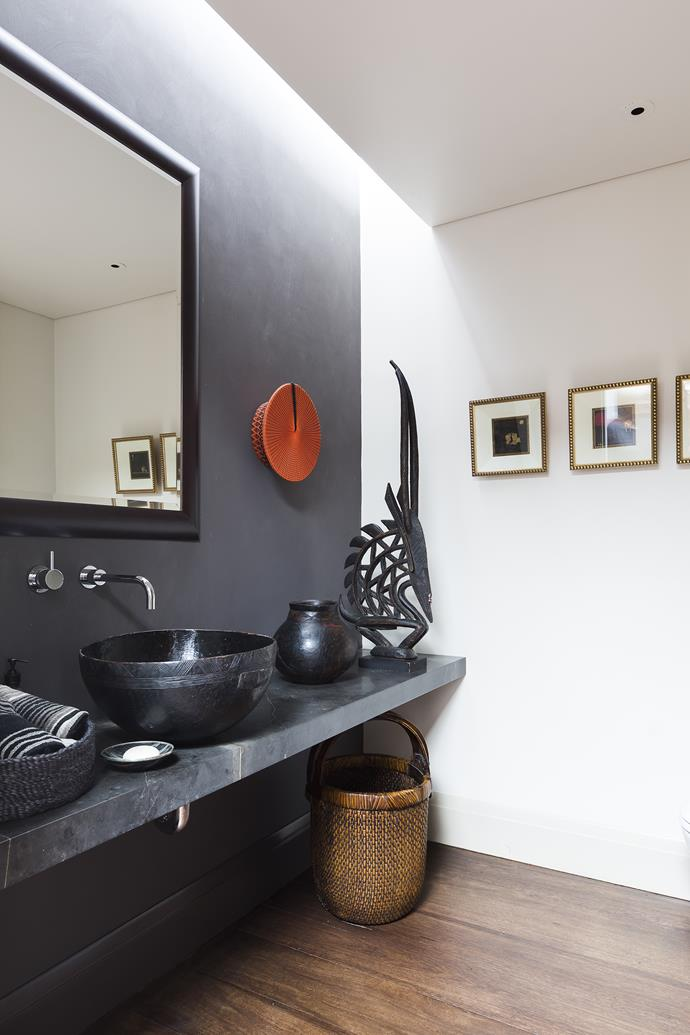 """For the guest powder room basin, Meryl drilled a hole in an African wooden bowl and coated it in silicone. """"I tend to go for dirty colours and use red in small doses as the lipstick for the room,"""" she says."""