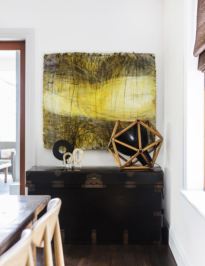 A painting by Joanne Kitas brings a blank wall by the dining table to life.