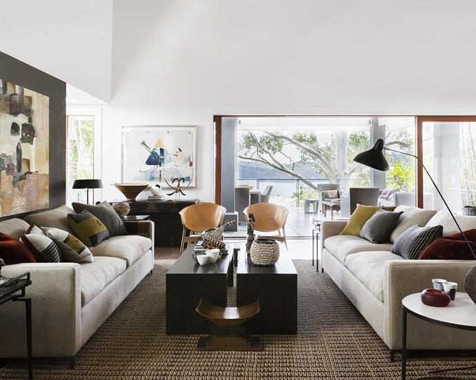 """The stylish living area has the family's talents on display. The Black Pot photographic artwork on the far wall is by daughter Jenni, while the painting at left was part of daughter Niccii's HSC project. Leather Pocket chairs from [Stylecraft](http://www.stylecraft.com.au/?utm_campaign=supplier/ target=""""_blank""""), Mantis floor **lamp** from [Spence & Lyda](http://www.spenceandlyda.com.au/?utm_campaign=supplier/ target=""""_blank""""), **sofas** from [Hare+Klein](http://hareklein.com.au/?utm_campaign=supplier/ target=""""_blank"""")."""