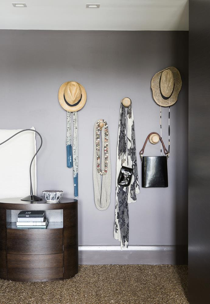 Accessories become art in the main bedroom, with the help of some simple wall hooks.