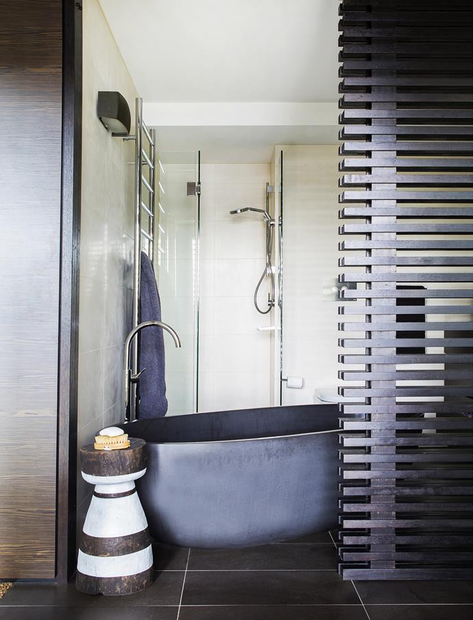 """The sliding timber screen lets in the light while affording bathtime privacy. **Bath** from [Apaiser](http://www.apaiser.com/?utm_campaign=supplier/ target=""""_blank""""), African **stool** from [Orient House](http://www.orienthouse.com.au/ target=""""_blank"""")."""