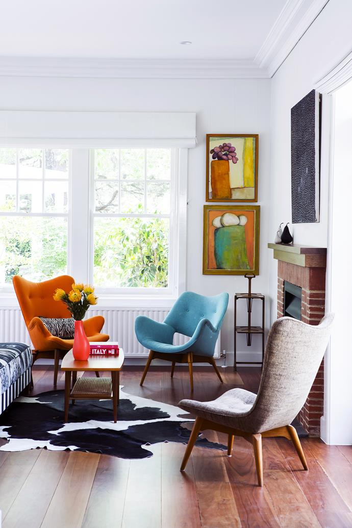 """""""We wanted classic designs with a contemporary edge,"""" says Belinda of the revamped Grant Featherston chairs. Featherston R160 (orange), B210H TV (blue) and R152 (grey) **chairs** from Revival Antiques & 20th Century Design. **Artworks** by Prue Hawke **[BESIDE WINDOW]** and Rusty Peters **(OVER MANTEL)**."""