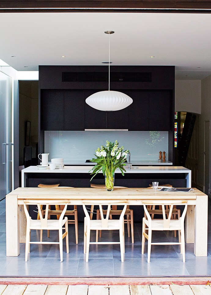 Sleek black cabinetry + square-edged timber table + glass splashback = stylish and inviting. Photo: James Braund / bauersyndication.com.au