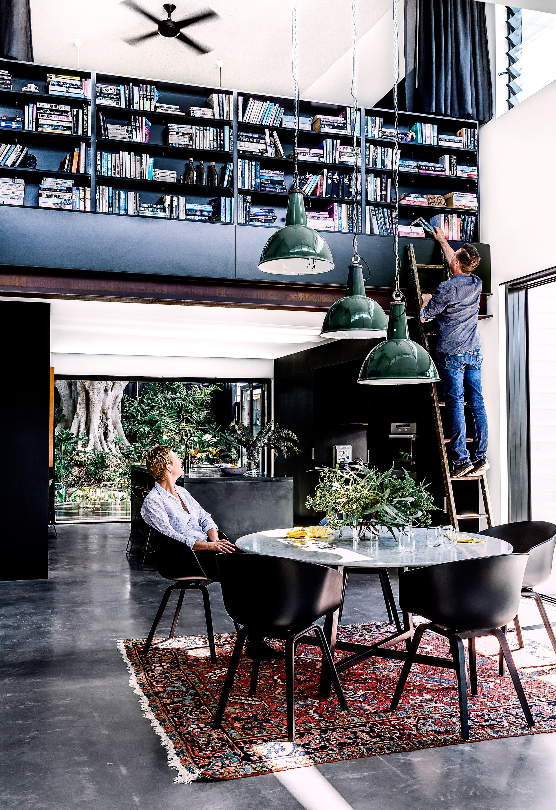 "A palette of dark, moody colours and industrial materials creates a look of urban sophistication in this Brisbane home. Achieving a good spatial flow throughout the living areas was key. The elevated library is still easily accessible thanks to an antique ladder from [Hobohemia](http://www.hobohemia.com.au/|target=""_blank""). Photo: Maree Homer / *Australian House & Garden*"