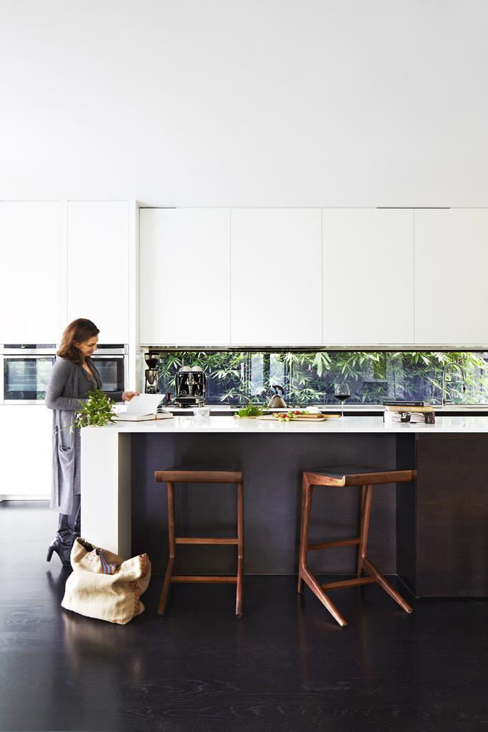 """Kylie at the long Corian benchtop, which affords her ample working space. To the right of the bench is a concealed butler's pantry. """"With the amount of entertaining we do, it's wonderful to have a designated place for mess,"""" she says. **Stools**, [Clickon Furniture](http://www.clickonfurniture.com.au/?utm_campaign=supplier/
