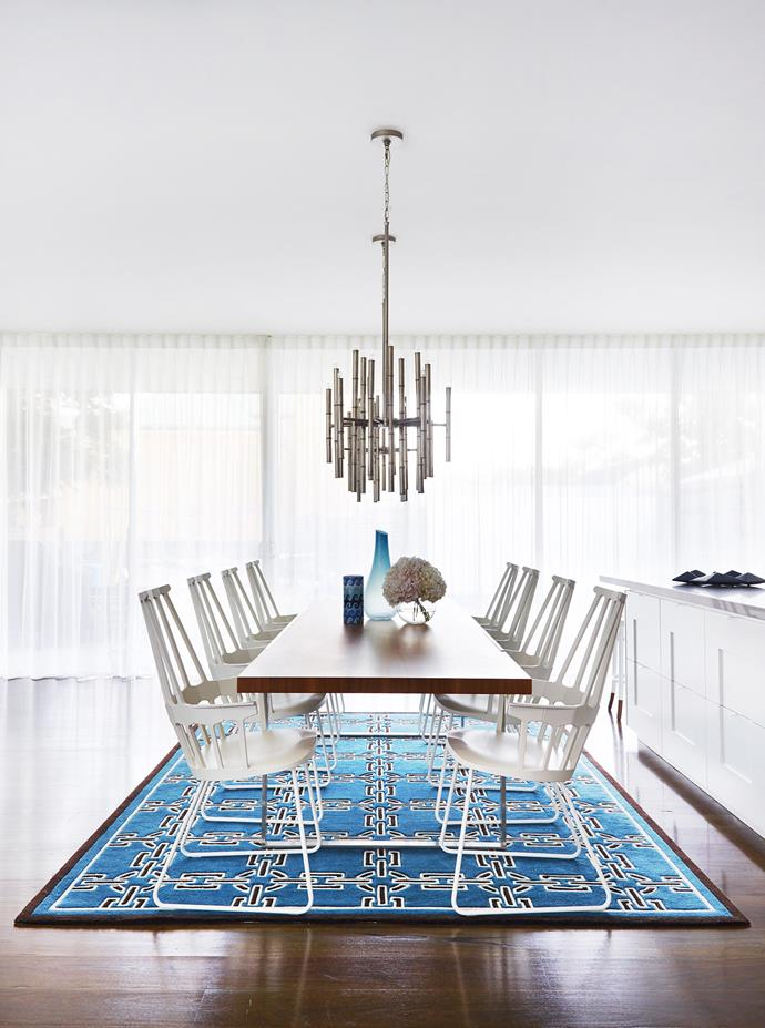 "The slatted backs of the Kartell dining chairs are subtly echoed in the linear form of a modernist light fitting overhead.   **Pendant light** from [Jonathan Adler](http://www.jonathanadler.com/?utm_campaign=supplier/|target=""_blank"")."