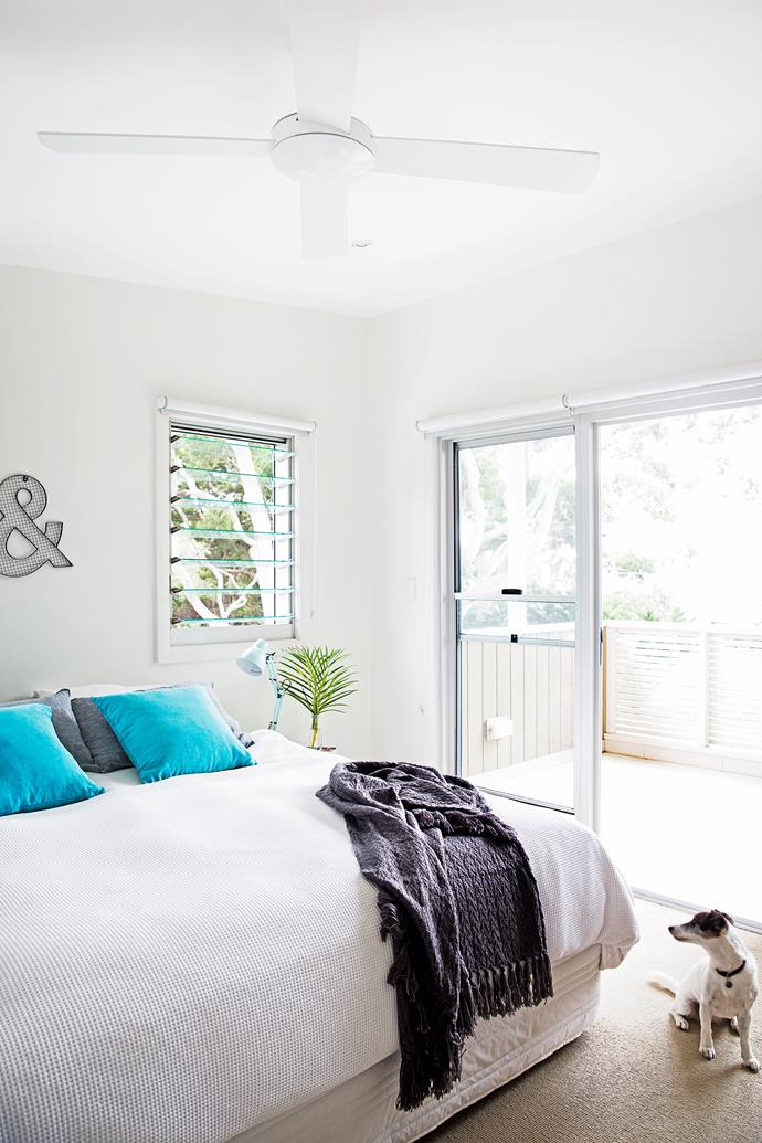 White walls and bedlinen are uplifted with cool blue and grey accents.