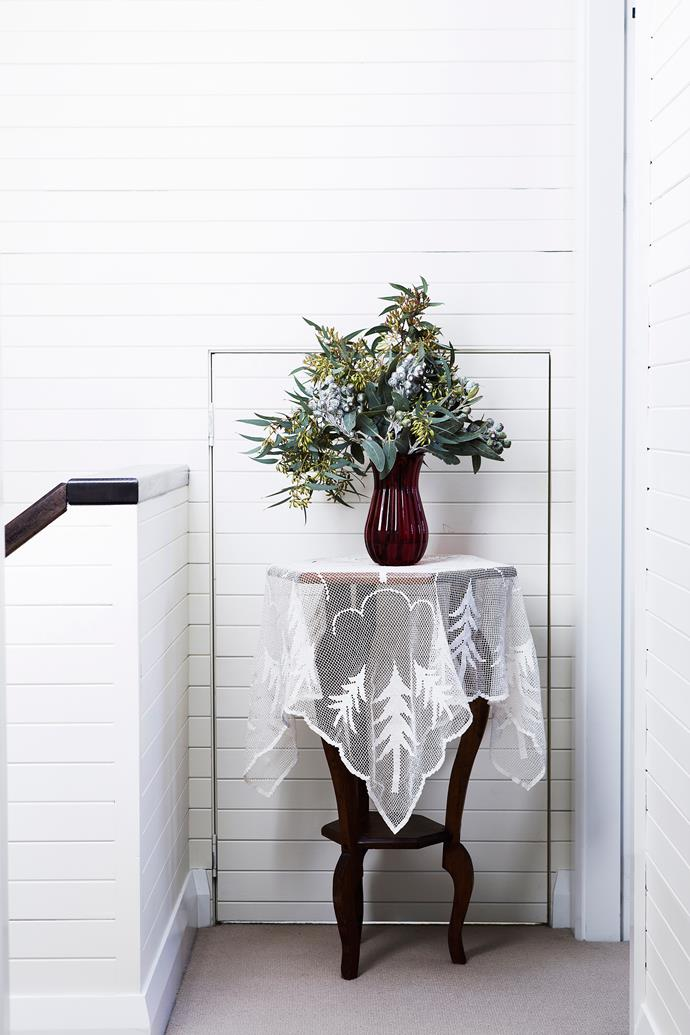 A table in the upstairs hall (part of the new extension), set with a vintage netted cloth and native flowers. The black, white and cream tones and dark timber come together perfectly to create the feeling of a beautiful and serene country house in the city. An attic playroom lies behind the 'secret' door.