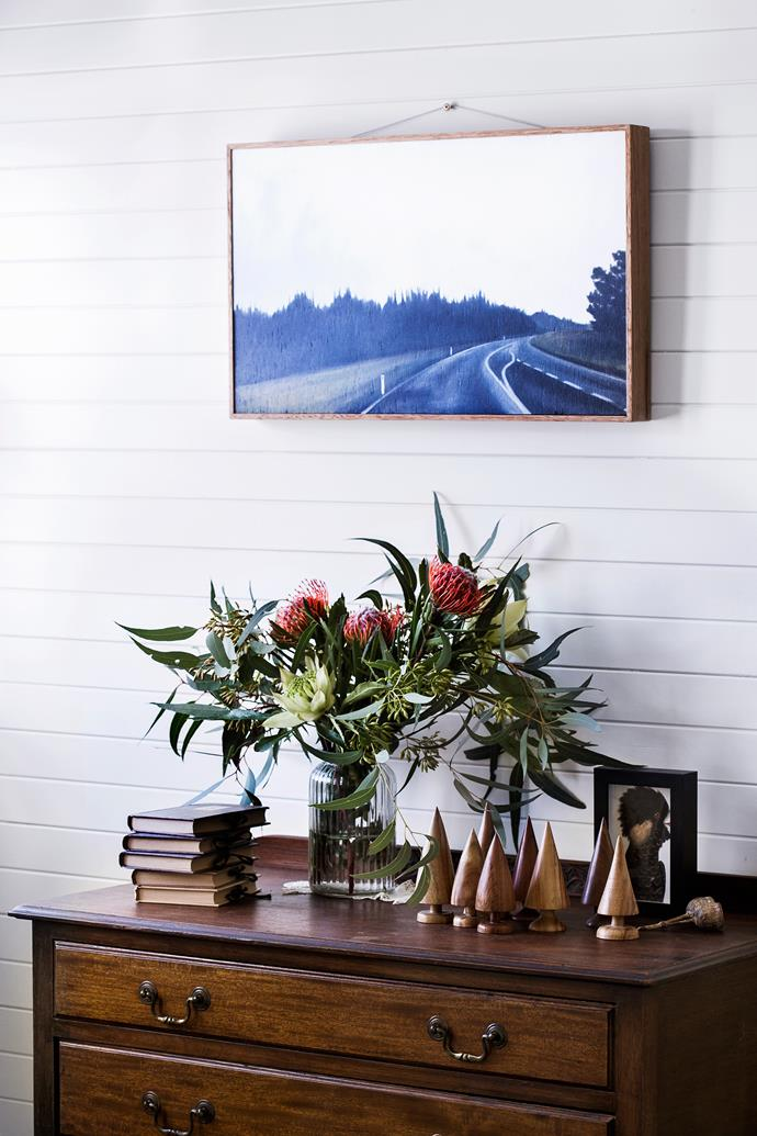 """In the bedroom, an antique sideboard is topped with native flowers. Little timber **trees** by Ray Mahoney from [Leura Fine Woodwork Gallery](http://www.finewoodwork.com.au/