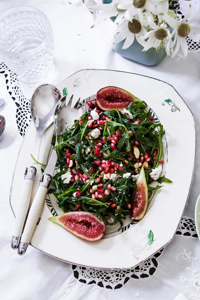 A pomegranate, fetta and rocket salad is presented with figs on a vintage plate and with Laguiole servers.