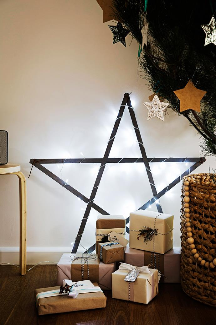 A star strung with fairy lights provides a backdrop for all those carefully wrapped gifts.