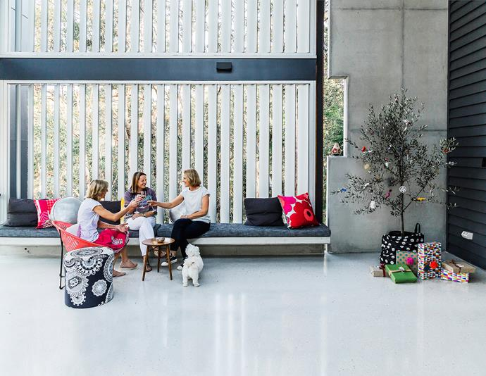 "Kylie (right) toasts the festive season with sisters Catherine and Megan (centre) watched by Mini. This airy space provides a retreat in the heat thanks to polished-concrete floors and louvres. **Pompoms** (on gifts) from [Lanternshop](http://www.lanternshop.com.au/?utm_campaign=supplier/|target=""_blank"")."